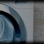 A washing machine standing against a white brick wall