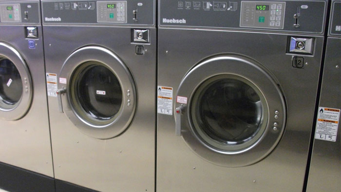 A row of stainless steel Huebsch washing machines in a laundromat