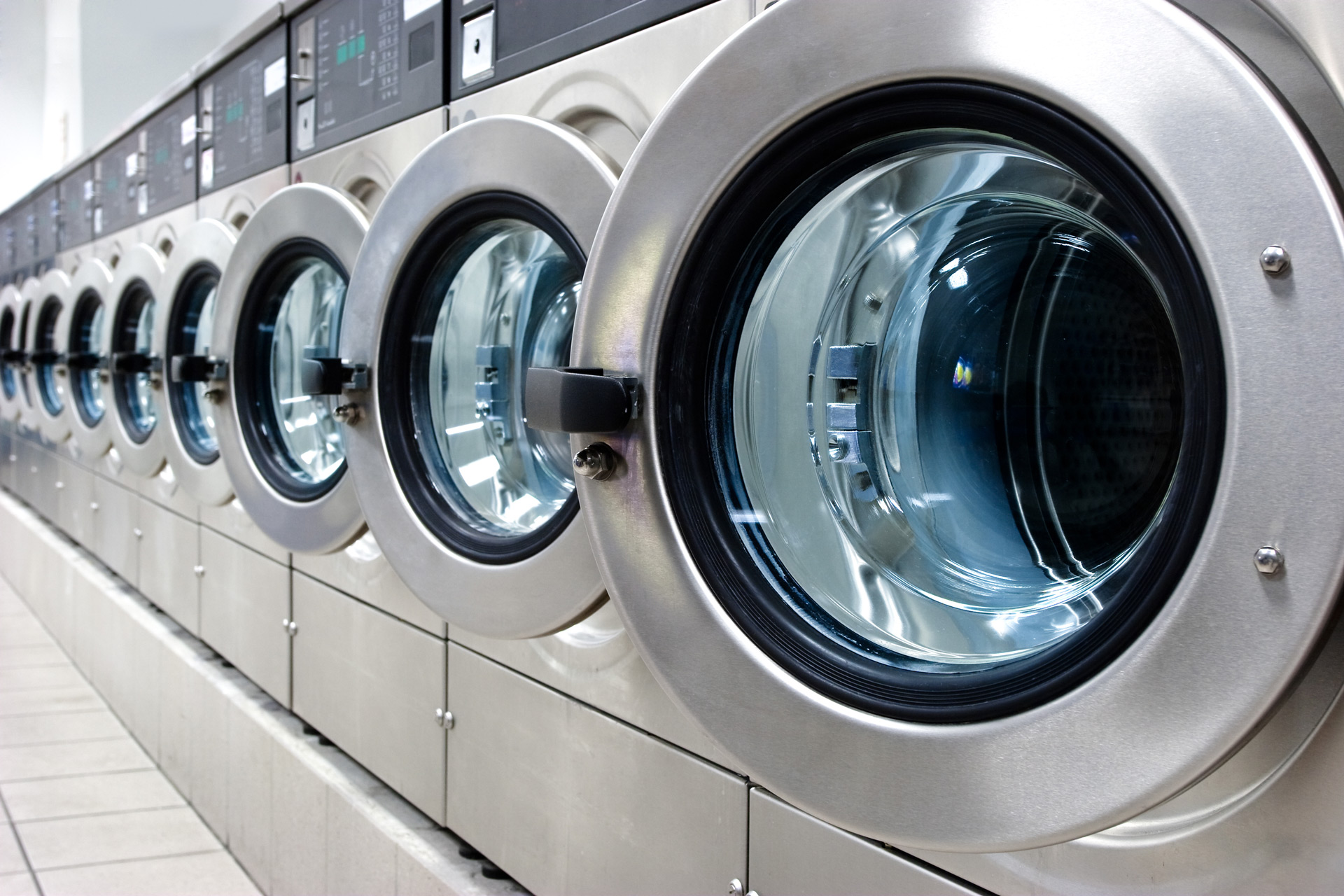 A row of stainless steel washing machines in a laundromat
