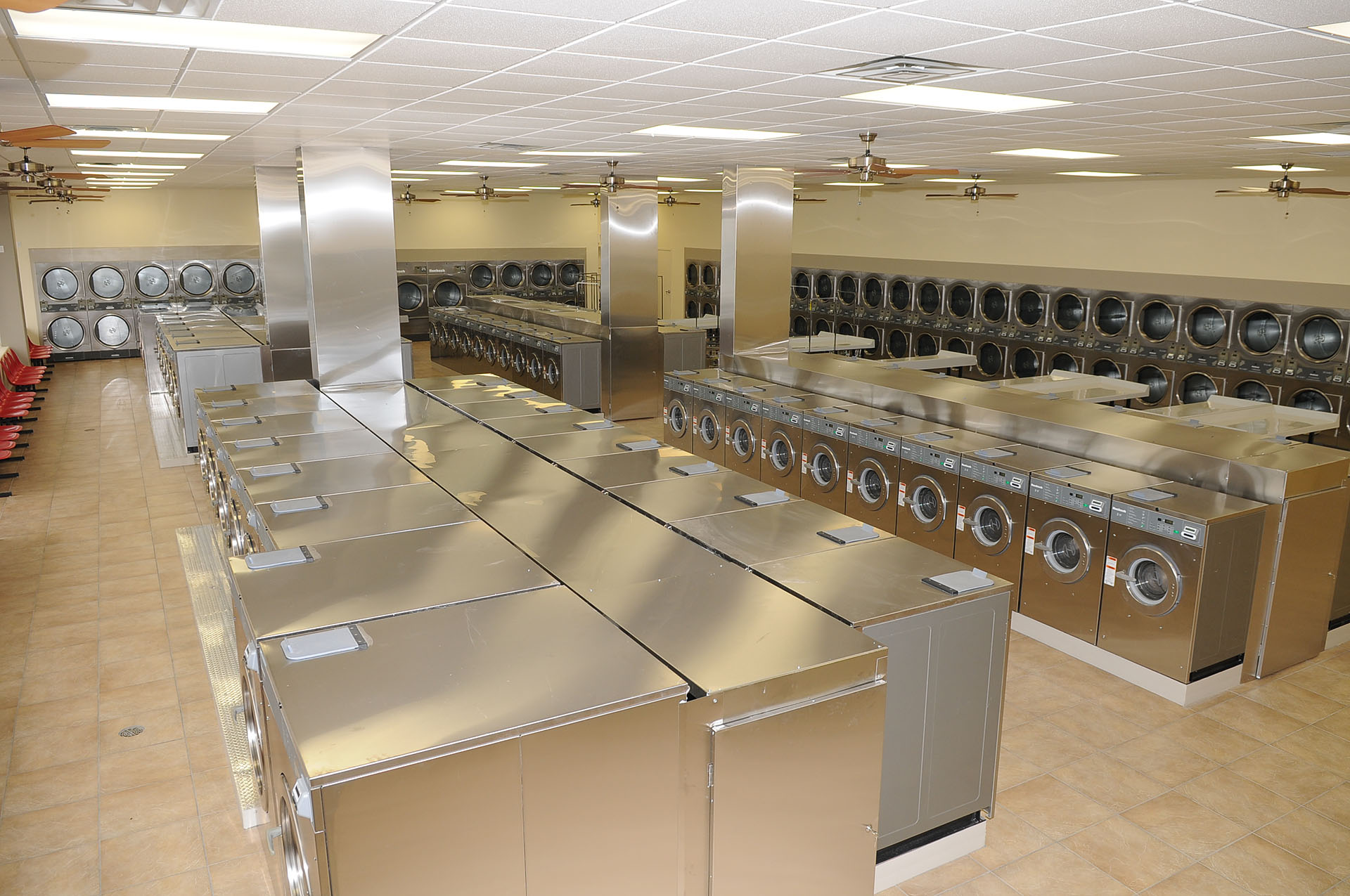 The inside of a laundromat with stainless steel washing machines and dryers